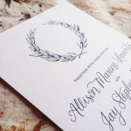 - AMY ROCHELLE PRESS - Detail view of olive crest and modern calligraphy on letterpress wedding invitation.