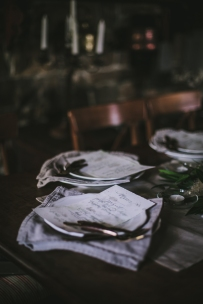 A gorgeous dinner tablescape styled by Eva Kosmas Flores with neutral linens, rustic silverware and touches of green for the centerpiece | Photo by Eva Kosmas Flores | AMY ROCHELLE PRESS