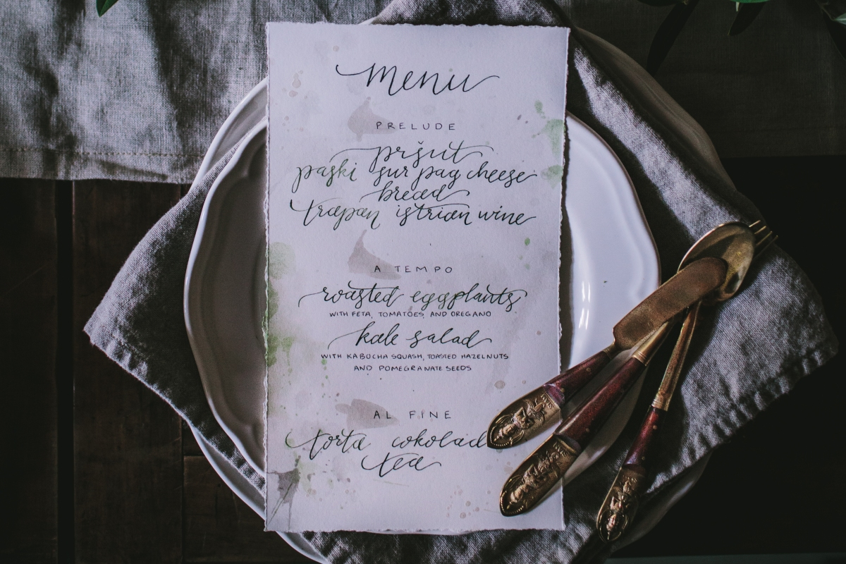 Detailed shot of calligraphy menus showing deckled edges, pearl accents, and soft gray and emerald ink. Each course was hand lettered onto print paper | Photo by Eva Kosmas Flores | AMY ROCHELLE PRESS